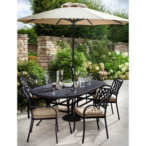 2019 Hartman Berkeley 6 Seater Oval Garden Dining Table Set In Situ With 6 Outdoor Dining Chairs And An Open Solar Parasol