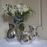 Set of 3 silver hammered jugs side view on table cloth with vase of flowers