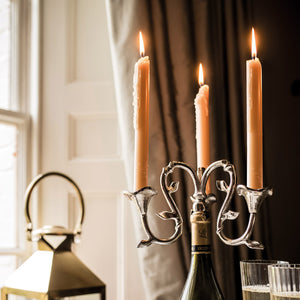close up of wine bottle candelabra on table with candles lit