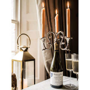 wine bottle candelabra on table with candles lit