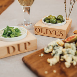 Olive dish with four picks in situ with olives on busy table