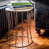 Iron and marble side table in room with wooden floor, close up with books on top