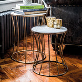 Iron and marble side table in room with wooden floor, with mugs and books on top