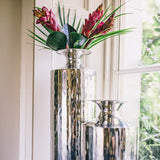 Tall metal vase on window sill with other silver items and flowers