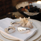 Metal mussel tweezers trio on napkin and set table
