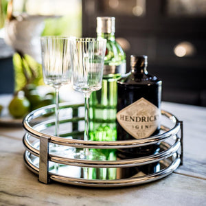 Round drinks tray with a bottle of Hendricks gin and two wine glasses on it