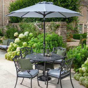 2019 Hartman Capri Antique Grey 4 Seater Round Garden Dining Table, Dining Chairs With Platinum Faux Leather Outdoor Cushions, And Open Solar Parasol In Situ