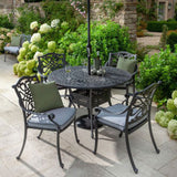 Glasses Of Wine Stood On The 2019 Hartman Capri Antique Grey 4 Seater Round Garden Dining Table Surrounded By Dining Chairs With Platinum Faux Leather Outdoor Cushions