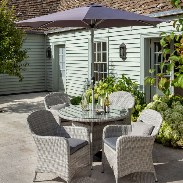 2019 Hartman Curve 4 Seat Round Garden Dining Table Set - Cool Grey / Charcoal on patio in front of house with tree and plants
