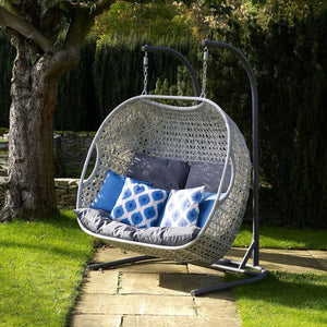 2019 Bramblecrest Monterey Double Hanging Cocoon Chair With Charcoal Cushions on pathway in front of large tree with blue patterned cushions