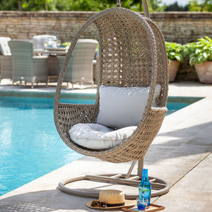 2019 Hartman Heritage Outdoor Hanging Chair With Weatherready Cushion - Beech/Dove on patio in front of pool and brick wall