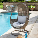2019 Hartman Heritage Outdoor Hanging Chair With Weatherready Cushion in front of pool with bottle and hat on patio