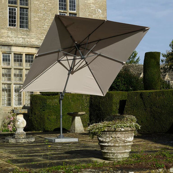 2019 Bramblecrest Lichfield Square Side Post Parasol in front of stone brick house and shaped hedge