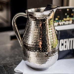 Stainless steel tall jug with dimpled surface sat on a white napkin on a dining table