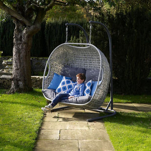 2019 Bramblecrest Monterey Double Hanging Cocoon Chair With Charcoal Cushions on path in front of large tree with boy sat on chair