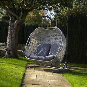 2019 Bramblecrest Monterey Double Hanging Cocoon Chair With Charcoal Cushions on path in front of large tree with plain grey cushions