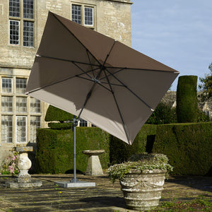 Full inside view of 2019 Bramblecrest Lichfield Square Side Post Parasol in front of stone brick house and shaped hedge