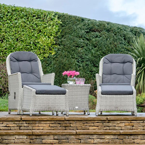 2019 Bramblecrest Monterey Outdoor Reclining Chair Set With Ceramic Top Side Table on raised steps in front of large hedge