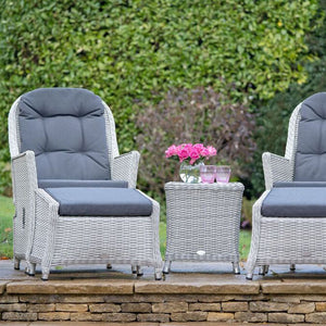 2019 Bramblecrest Monterey Outdoor Reclining Chair Set With Ceramic Top Side Table in front of large hedge with flowers on table