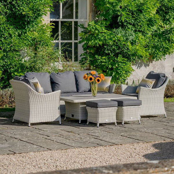 2019 Bramblecrest Monterey 3 Seat Outdoor Sofa Set With Adjustable Ceramic Dining Table on patio in front of house with plants on and sunflowers on table