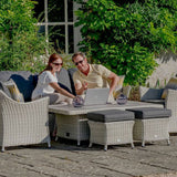 2019 Bramblecrest Monterey 3 Seat Outdoor Sofa Set With Adjustable Ceramic Dining Table with people sat at the table pointing at a laptop