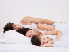 Natural-family-sleeping-together-white-sheets