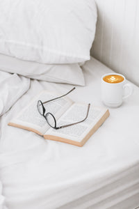 white sheet set with glasses book and coffee luna luxury