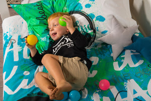 organic-cotton-quilt-cover-set-jammin-music-graffiti-speakers-green-single-display-boy lying-down-holding-balls
