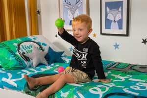 organic-cotton-quilt-cover-set-jammin-music-graffiti-speakers-green-single-display-boy sitting-holding-ball
