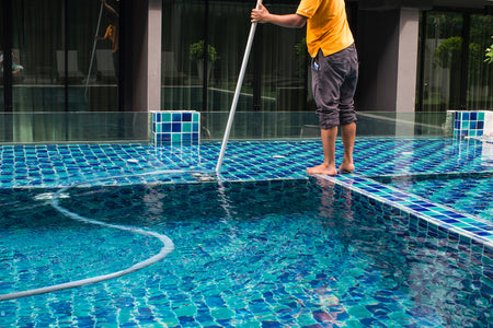 Man vacuuming his pool.