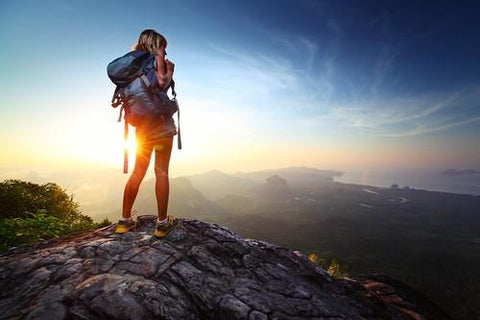hiker on a mountain with a sunset