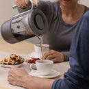 tea brewer woman pouring tea in cup
