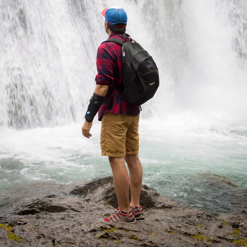 wearable water container man next to waterfall