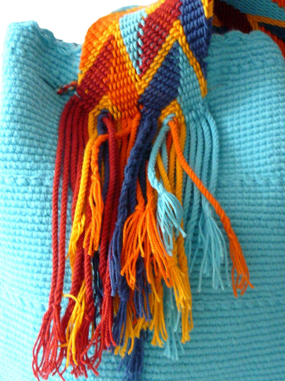 Turquoise woven shoulder bag with blue, orange, and yellow tassels Palmazul Beachwear Wayuu Mochila