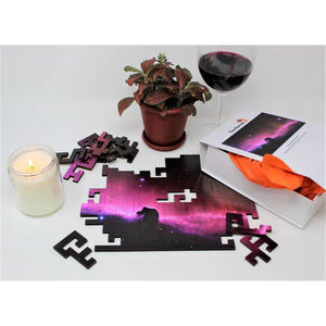 Puzzle being assembled on a table with a candle, plant, and glass of wine.