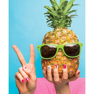 Hands with assorted nail colors and patterns on each hand, holding a pineapple with green sunglasses.