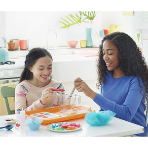 Two young women making soap jellies in a white kitchen.