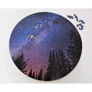 Puzzle with four pieces missing and off to the side. Image of pine trees silhouetted agains a night sky.