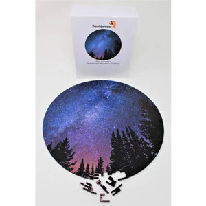 Puzzle with the silhouette of treetops agains a vibrant blue and purple night sky