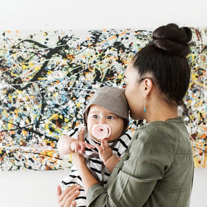 Woman with a dark bun, holding an infant with a blush pacifier, in front of a modern painting.