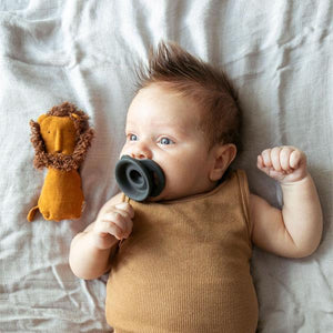 Baby with a shock of reddish brown hair and a gray pacifier in their mouth.