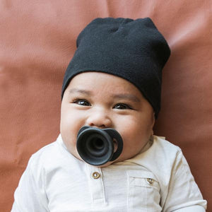 Smiling baby with a grey hat and a grey pacifier in his mouth.