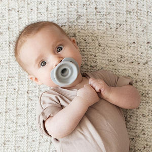 Sweet baby with hands clasped to their chest with a grey pacifier in their mouth.
