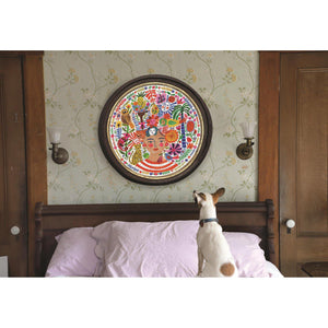 Jack Russel dog sitting on a bed with pink sheets, looking up at the framed and assembled puzzle on the wall