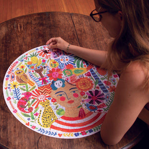 Woman assembling the puzzle featuring image of woman with rosy cheeks and a red and white striped shirt, surrounded by bright animals and flowers