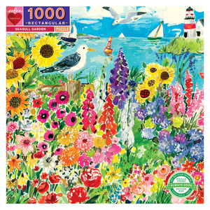 Colorful Seagull Garden puzzle box, image features bright flowers in the forefront and the ocean with boats and a lighthouse in the back with seagulls flying and standing