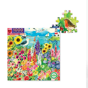 Colorful Seagull Garden puzzle box, image features bright flowers in the forefront and the ocean with boats and a lighthouse in the back with seagulls flying and standing and a detail of an assembled portion of the puzzle