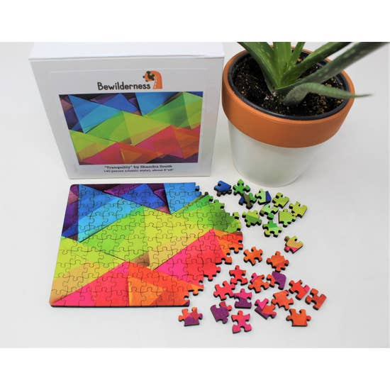 Puzzle box with partially assembled puzzle featuring translucent, rainbow-colored, overlapping triangles.