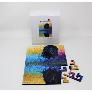 Box with mostly assembled puzzle, depicting a black raven admiring his own reflection on a blue, yellow, orange and magenta, painterly background.