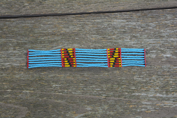 Bright turquoise colored Masai bracelet with red, black and yellow pattern
